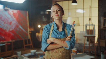 Fototapete - Portrait of Young Female Artist Dirty with Paint, Wearing Apron, Crosses Arms while Holding Brushes, Looks at Camera with Smile. Authentic Creative Studio with Large Canvas and Tools Everywhere