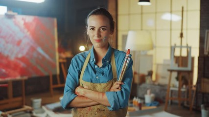 Fototapete - Talented Young Female Artist Dirty with Paint, Wearing Apron, Crosses Arms while Holding Brushes, Looks at the Camera with a Smile. Authentic Creative Studio with Large Canvas. Face Portrait