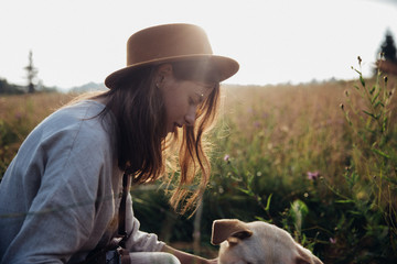 Girl and her friend dog are playing on the straw field background. Beautiful young woman relaxed and carefree enjoying a summer sunset with her lovely dog Fototapete