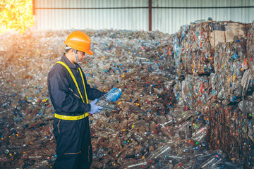 Engineer checking second hand plastic bottles In the background, slalom yards in bottle recycling industry Wall mural