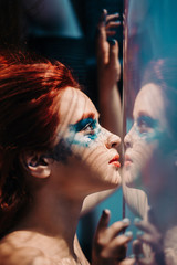 Surreal portrait of red haired girl like a mermaid behind the glass with under water effects. asking for help