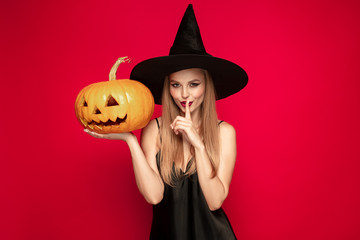 Young blonde woman in black hat and costume on red background. Attractive caucasian female model. Halloween, black friday, cyber monday, sales, autumn concept. Copyspace. Holds pumpkin. Fototapete
