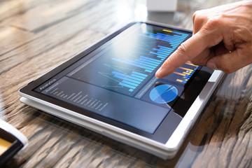 Businessman Analyzing Graph On Convertible Laptop