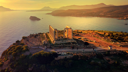 Aerial drone photo of sunset over the iconic Temple of Poseidon at Cape Sounio with amazing golden colours, Attica, Greece