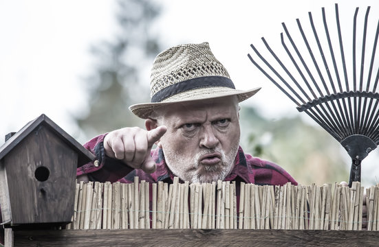 An evil, aggressive man watches his neighborhood over the garden fence. Concept dispute and aggression between people.