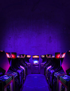 Old Unbranded Vintage Arcade Video Games in dark gaming room with purple light with glowing displays and concrete wall - vertical photo of retro design with free copy space for a poster or magazine