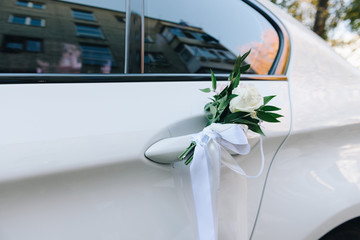 A close-up picture of a white wedding car door