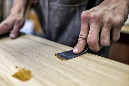 Putty knife in man hand. Removing holes from a wood surface. Preparation of boards before impregnation with varnish.