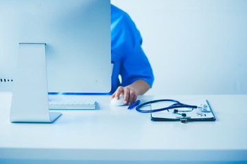 Unknown doctor woman filling up medical form while sitting at the desk in hospital office