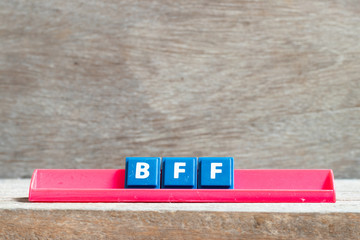 Tile letter on red rack in word BFF (Abbreviation of best friend forever) on wood background