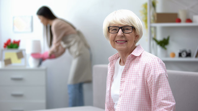 Smiling aged woman looking at camera, housekeeper wiping dust in room, cleaning