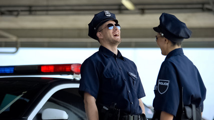 Young police officers laughing standing near car, successful patrol shift