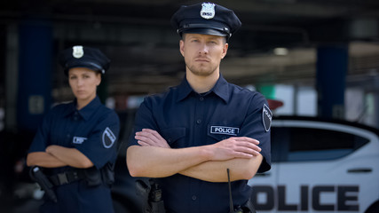 Confident male and female police officers in uniform standing near patrol car