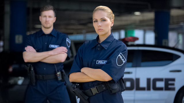 Qualified police officers posing on background of patrol car, criminal justice