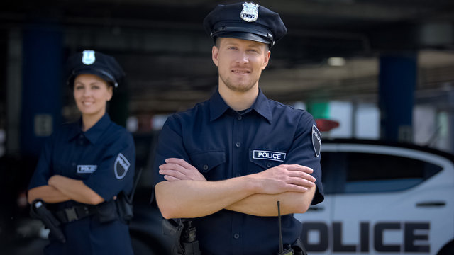 Kind police officers smiling standing near police station, ready to help, order