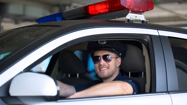 Young policeman in sunglasses sitting in car smiling into camera, important job