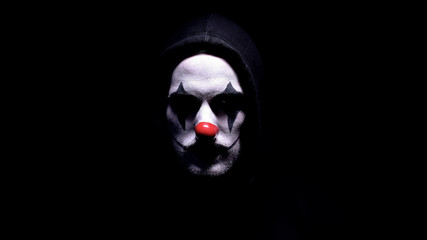 Spooky clown in hoodie looking at camera, black background, criminal disguise