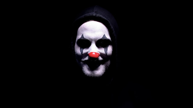 Maniac with spooky clown face angrily smiling into camera, psycho threatening