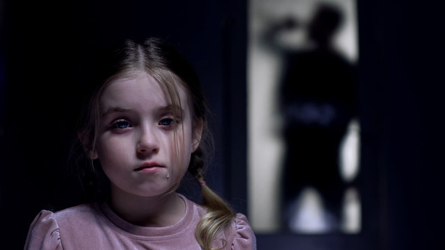 Crying little girl looking at camera silhouette of alcoholic father outside door