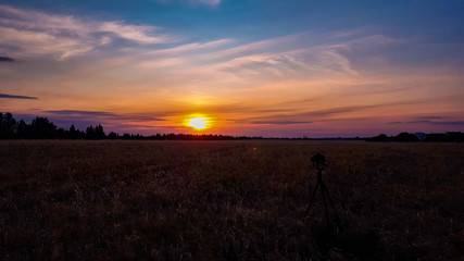 Fototapete - Silhouette of camera on tripod capturing sunset over the wheat field. Photographing an evening landscape. Camera the night view.