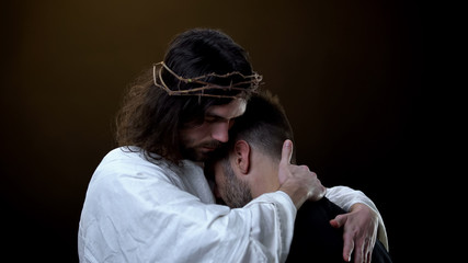 Savior in crown of thrones hugging desperate male, religious peace, forgiveness Wall mural