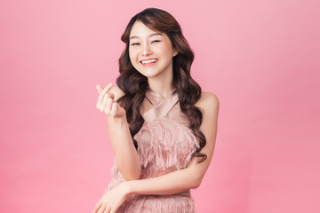 Image of charming woman 20s wearing dress smiling and standing isolated over pink background