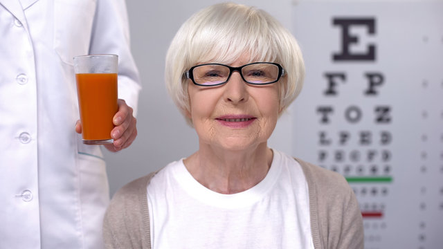 Optician giving fresh carrot juice to happy aged lady, maintaining good vision