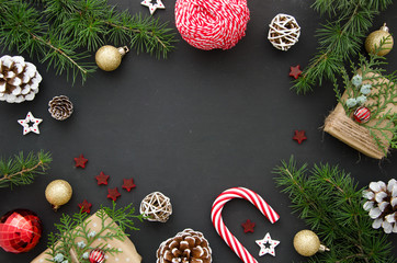 Christmas flat lay decoration background: fir-tree branches, golden and silver balls, candy cane on black background. Mockup with copy space Wall mural