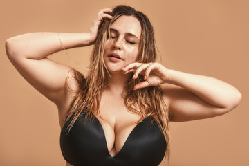 Natural beauty. Portrait of a plump woman in black underwear touching her hair and keeping eyes closed while standing against brown wall in studio