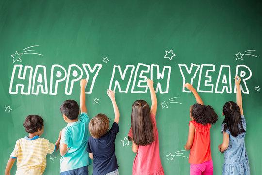 school children drawing happy new year on the chalkboard