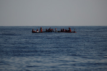 RHIBs of the German NGO Sea-Eye migrant rescue ship 'Alan Kurdi' rescue migrants claiming to be Tunisians from a small wooden boat in the central Mediterranean Sea