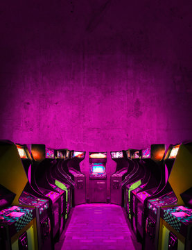 Old Unbranded Vintage Arcade Video Games in a dark gaming room with pink light with glowing displays and concrete wall - vertical photo of retro design with free copy space for a poster or magazine