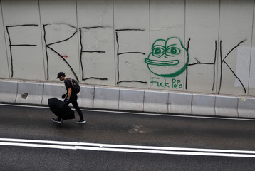 A demonstrator walks past a graffiti on a wall during a protest in Hong Kong