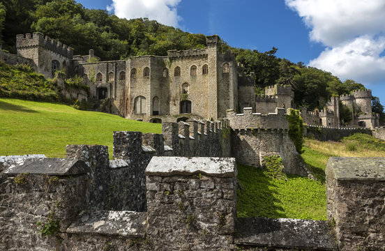 Gwrych castle in Wales UK surrounded by trees and foliage on hill side ruins.