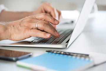 Closeup of businessman's hands working with laptop