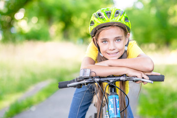 Portrait of a little girl riding her bike,  looking at camera and smiling. Empty space for text