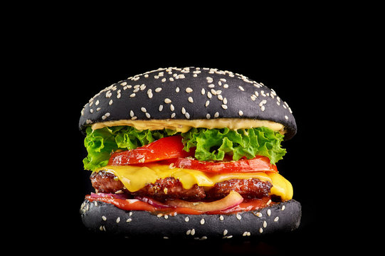 black burger at black background with beef or pork cutlet or steak with fried tomatoes, cheddar, cheese sauce, lettuce and ketchup in black bun with cuttlefish ink sprinkled with sesame