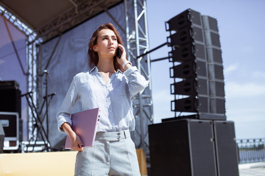 Installation of stage equipment and preparing for a live concert open air. Event manager portrait. Summer music city festival. Young serious woman stand and work with her laptop near the stage...