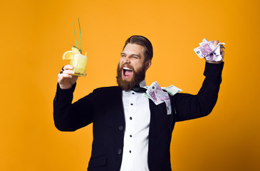 Happy young businessman with glass of cocktail in formal clothes holding bunch of money banknotes