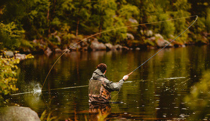 Papiers peints Peche Fisherman using rod fly fishing in mountain river