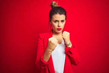 Young beautiful business woman standing over red isolated background Ready to fight with fist defense gesture, angry and upset face, afraid of problem