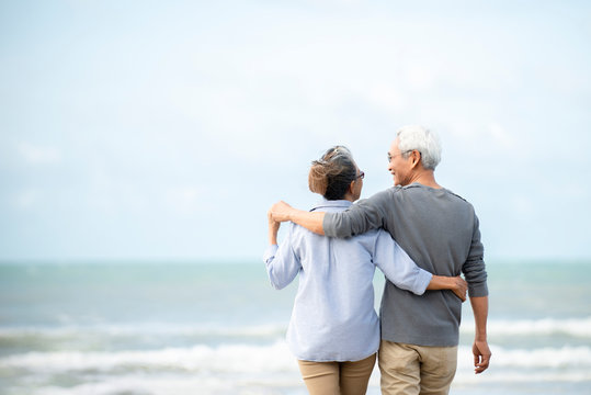 Happy asian senior couple  have fun and enjoy at the beach, senior man and woman hugging while walking on the beach Retirement Lifestyle Healthy  Travel Vacation Concept