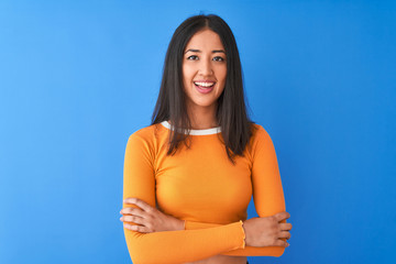 Young beautiful chinese woman wearing orange t-shirt standing over isolated blue background happy...