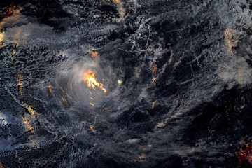 Hurricane at night over land burning in fires. Elements of this image furnished by NASA.