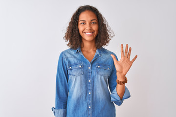 Young brazilian woman wearing denim shirt standing over isolated white background showing and pointing up with fingers number five while smiling confident and happy.