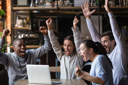 Euphoric diverse friends celebrating victory watching online game on laptop