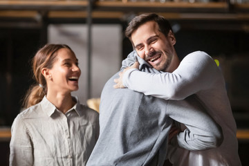 Happy diverse male buddies embracing laughing greeting in cafe