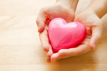 Hands holding pink heart with wooden background