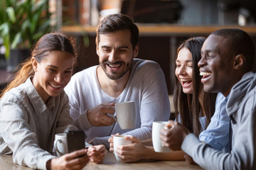 Happy diverse friends taking group selfie on cellphone in cafe Wall mural