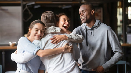 Excited diverse friends embrace greeting male buddy coming at meeting Wall mural